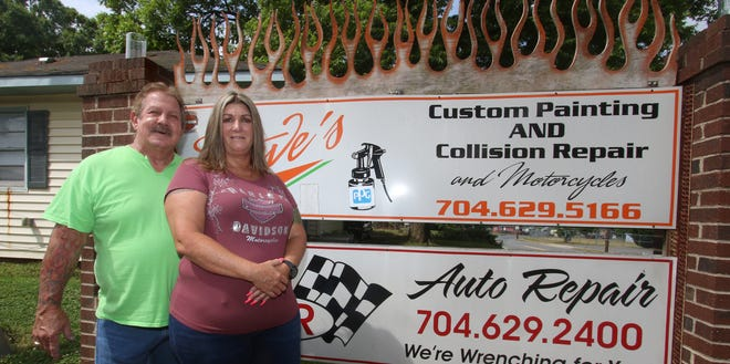 Steve and Sandy Jenkins stand outside their shop on Gastonia Highway in Bessemer City as Steve's Paint and Body celebrates 50 years in business this week.