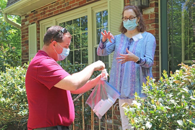 Jim Starbard, Massachusetts state lead for RCAP Solutions, demonstrates for a homeowner how water samples are collected for testing.
