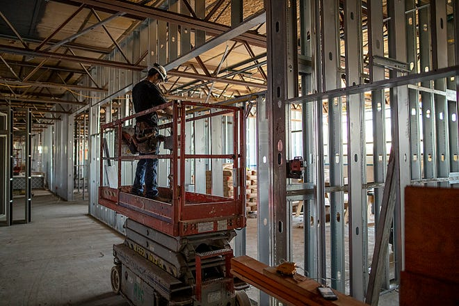 A worker takes measurements near under-construction classroom frames in the old vocational center area at Galesburg High School on Thursday, June 3, 2021.