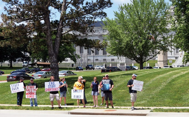Representatives of Local 919 of the American Federation of Government Employees hold up signs during an informational picket Friday in front of the U.S. Penitentiary in Leavenworth. The picketers expressed concern about the staffing level at the federal prison.