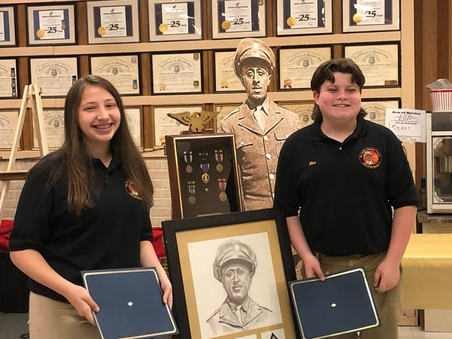 Aubrey Stewart Junior Ambassadors Kylie Keplinger and Max Ellifritz pose for a photo with a portrait of Aubrey Stewart, along with a display of his medals.