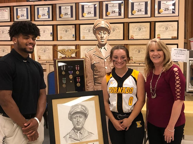 Keyser High School principal Lois Spencer (right) congratulates Aubrey Stewart Scholarship recipients Drae Allen and Carlie DelSignore, who had come straight to the awards dinner from her softball game.