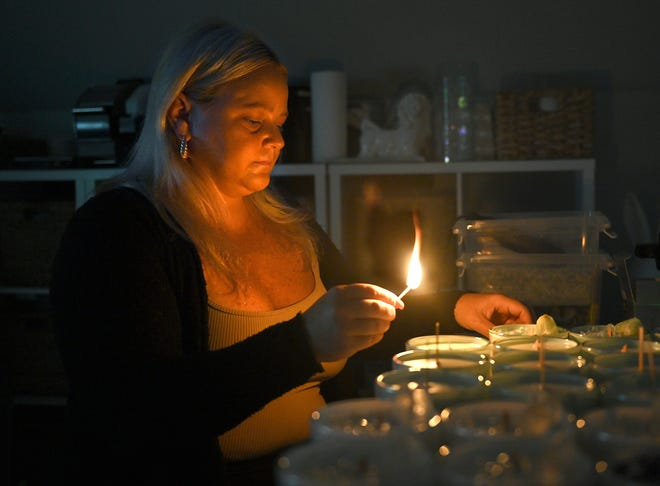 Lex Dascoli, owner of Vibes Candles, lights one of her candles in her Marlboro workshop.