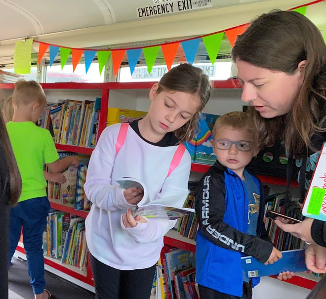 Mustang Schools students check out the book selection in the Bronco Bus parked at Riverwood Elementary School.