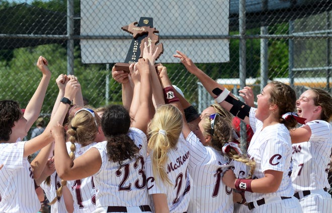 Charlevoix players hoist the Division 3 district championship trophy on their home field Friday after defeating Boyne City in five innings, 15-1.