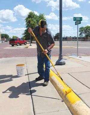 Scott Huffman is hard at work in the summer heat painting curbs yellow throughout Pratt as part of a citywide spruce-up plan.