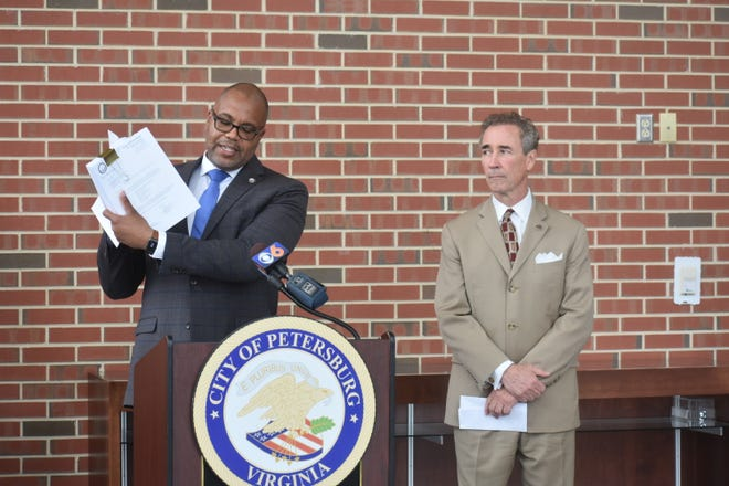 Petersburg Mayor Sam Parham holds a copy of the 267-page complaint filed against the owner of the blighted old Ramada Inn.