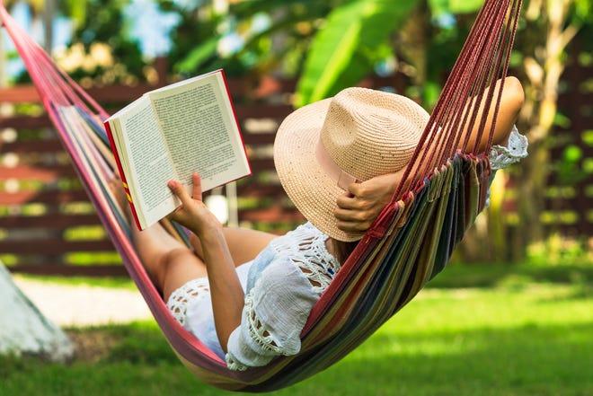 Woman reading book in hammock in tropical garden