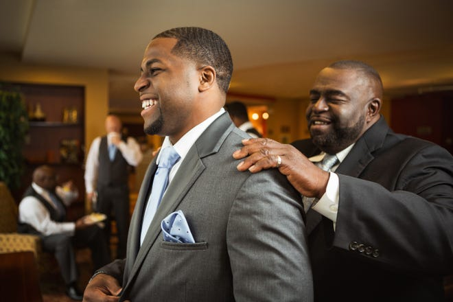 Father of the groom helping his sone get dressed