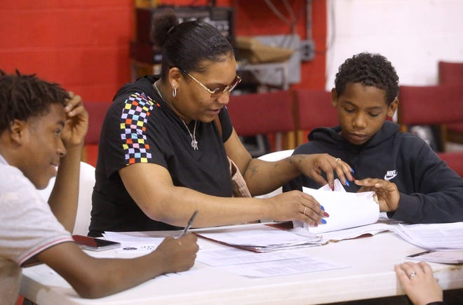 Teressa Bendson, center, helps her sons Kyzia Green, left,) and Kar'on Green during Simply Youth's orientation Thursday at the Kingdom Center. A new collaborative program, which involves morning summer school and afternoon work experience, begins Monday.
