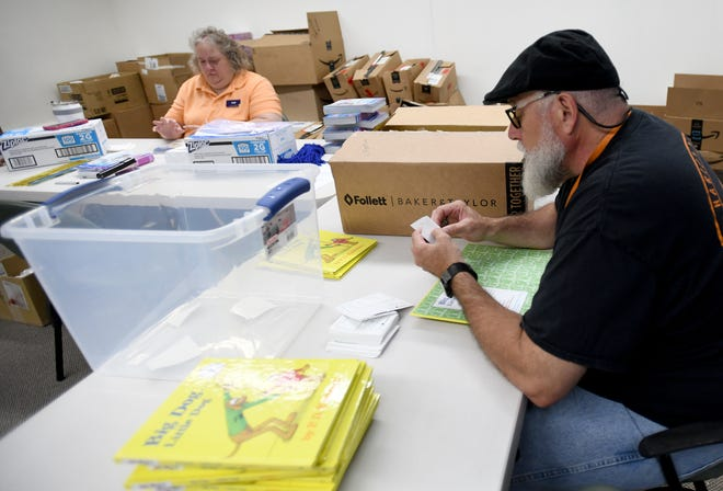 Stark County Public Library staff, including Tony Magisano, right, package activities bags at the main campus for the kids summer reading program. Friday, June 4, 2021.