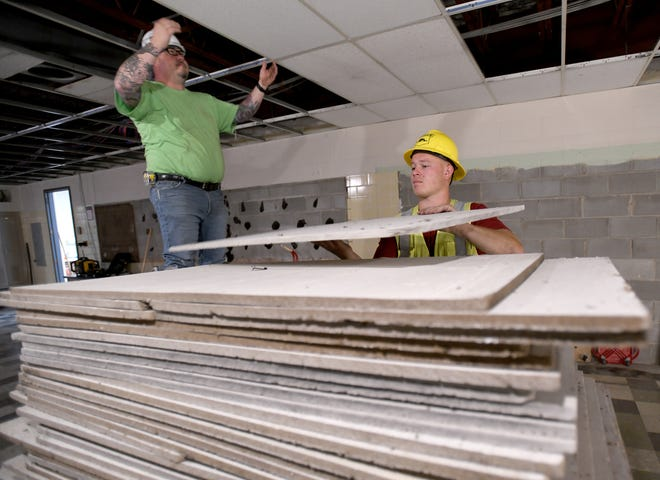 Curt Meffert and Gunther Soehnlen with Beaver Constructors Inc. remove ceiling tiles as work begins at Faircrest Middle School to convert the building into an elementary school. Canton Local is building a new middle school.