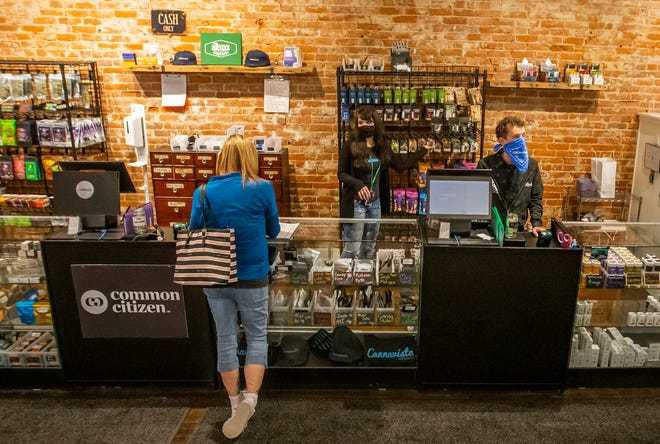 Employees of Cannavista Wellness, a marijuana shop and dispensary in downtown Buchanan, help customers on a recent day.