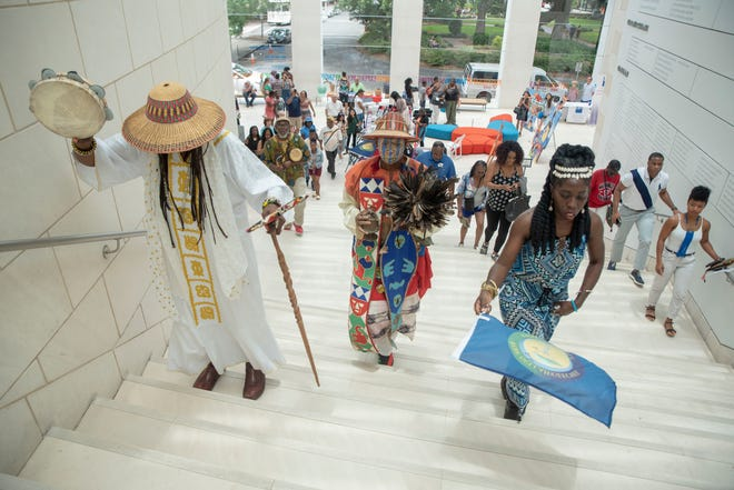 Participants of a  Juneteenth event, held at the Jepson Center For the Arts, walk up stairs.