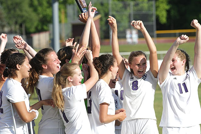The Three Rivers soccer team celebrates with the district trophy after beating Dowagiac in the district finals on Thursday evening in Niles-Brandywine.