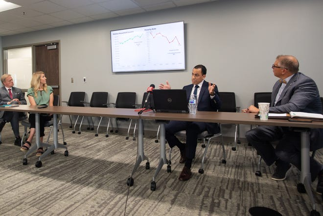 Freddy Mawyin, second from right, research manager for the Greater Topeka Partnership, presents U.S. Census data to members of the media during a roundtable discussion Friday at the GTP's headquarters.