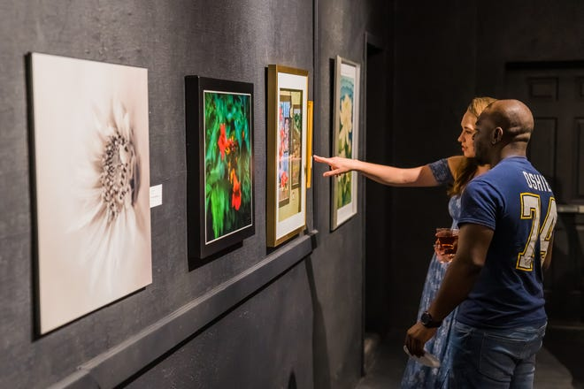 An attendee points to art on display during the 2019 Hays Arts Council Summer Art Walk. After a year off due to the pandemic, the event returns to downtown Hays this month.