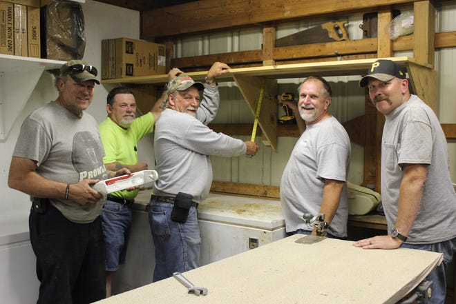 Berlin Volunteer Fire Department representatives Tim Rhoads, Rob Metheney, Bill Miller, Brad Flick and J.T. Kline put up a shelf for the upcoming Berlin Block Party, set for Wednesday through Thursday on the firemen's grounds in Berlin.