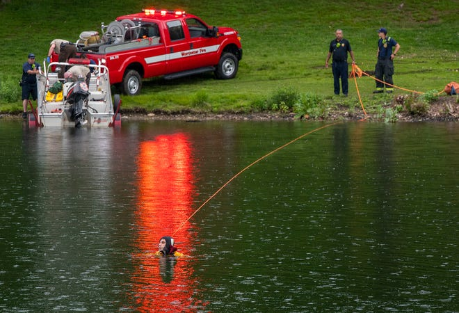 A Fire Department diver, foreground, searches Green Hill Pond.