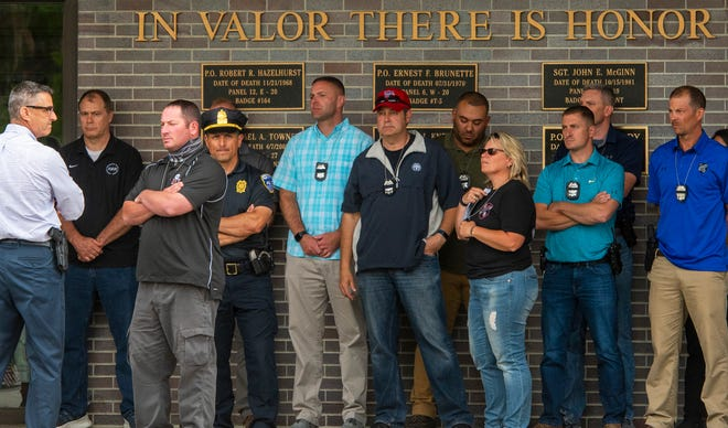 """During a news conference Friday at Worcester Police Department Headquarters on the death of Officer Enmanuel """"Manny"""" Familia, colleagues stood in front of a wall that honors fallen police officers."""