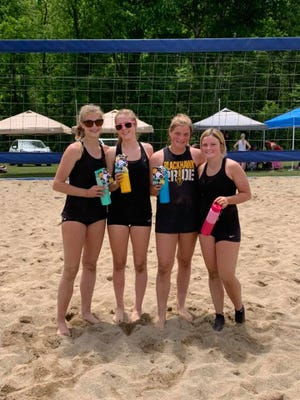 Springs Valley's Leigh Carnes and Brynne Buchanan (far right) celebrate their win at a sand volleyball tournament in Bedford on Monday.