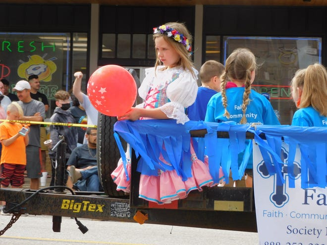 A little girl is dressed in traditional Czech attire riding a float during the National Polka Festival Parade in Ennis on Saturday.