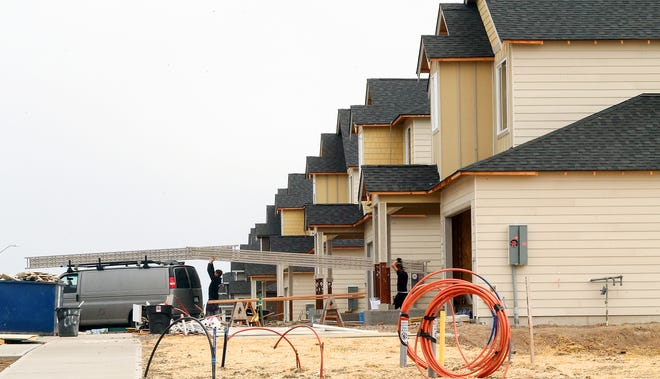 Scaffolding is loaded onto a van as crews work on a row of homes in the Soundview Estates development in Bremerton on June 3.