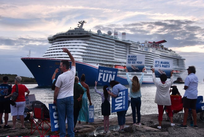 A crowd of thousands welcomes Mardi Gras, Carnival Cruise Line's biggest ship ever, as it arrives at Port Canaveral on June 4. Now Carnival will get the crew vaccinated against COVID-19 and await federal approval to take a test cruise.