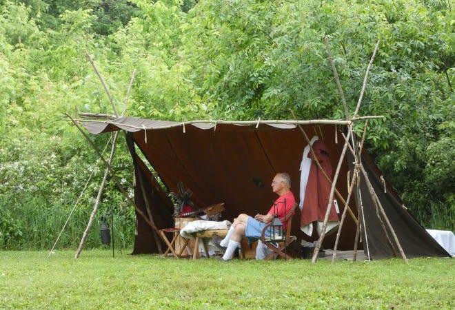 Reenactor Jack Barna of McKees Rocks, Pennsylvania, sits under his lean-to tent on Thursday evening at Lowe-Volk Park.