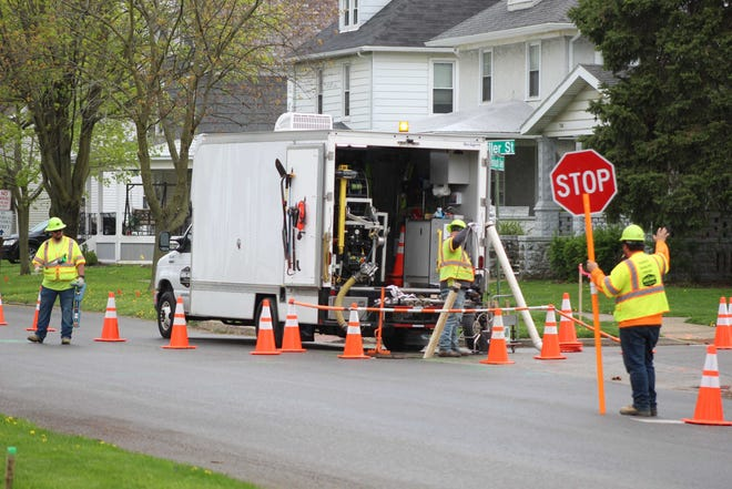 A crew from Mid-Ohio Pipeline Services works here in May 2020 on Rawson Avenue's road reconstruction project in Fremont. Fremont City Council members held a first reading Thursday on an ordinance for a new 0.5% income tax levy to help finance the city's proposed five-year road remediation program.
