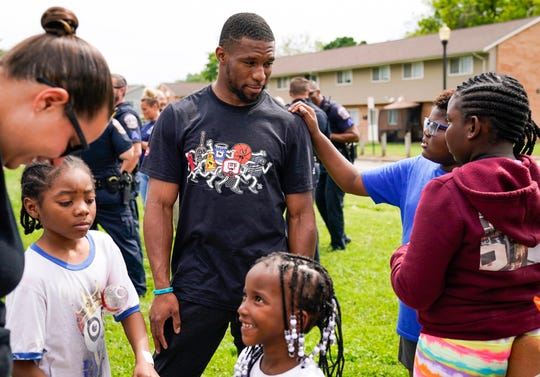 """Indianapolis Colts running back Nyheim Hines talks with kids of residents during a cookout held by members of the Indianapolis Metropolitan Police Department at the Blackburn Terrace apartments, Thursday, June 3, 2021, on Baltimore Avenue, Indianapolis. The """"Grill and Chill"""" with the Indianapolis Housing Agency and IMPD took place at Blackburn Terrace. This community and the surrounding neighborhood have seen an uptick in fatal and non-fatal shootings."""