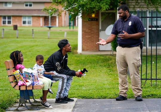 """An Indianapolis Metropolitan Police officer talks with a resident of Blackburn Terrace during a cookout, Thursday, June 3, 2021, on Baltimore Avenue, Indianapolis. The """"Grill and Chill"""" with the Indianapolis Housing Agency and IMPD took place at Blackburn Terrace. This community and the surrounding neighborhood have seen an uptick in fatal and non-fatal shootings."""