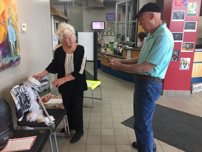 """Shirley Fearn shows off her chair at the Richland Academy of the Art while husband Clifford takes her picture. She titled the chair """"A Life in Dance"""" and used leftover material from dance costumes for the seat, which was adorned with a glittery derby, white feather boa and cane."""
