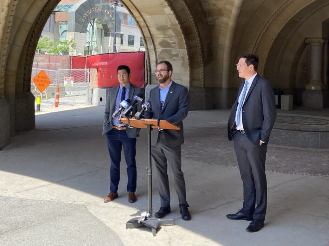 Milwaukee County Supervisor Ryan Clancy, flanked by his attorneys, Edgar Lin, left, and Drew DeVinney, right, announces details of his lawsuit against the city and county of Milwaukee on Friday.