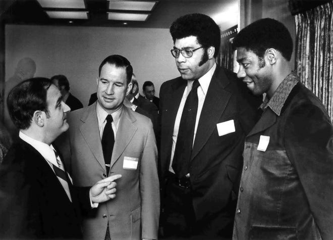 Dr. George Korkos, left, the Milwaukee Bucks' team physician and a member of the Bucks' board of directors, speaks with coach Larry Costello; Wayne Embry, the club's general manager; and Oscar Robertson, its star guard, in 1972.