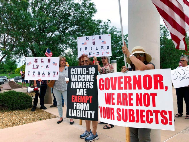 Protesters gather outside the Albuquerque Museum on Thursday, June 3, 2021, ahead of New Mexico Gov. Michelle Lujan Grisham's first major campaign rally as the Democrat seeks reelection.