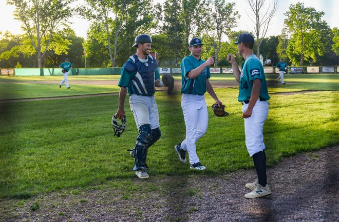 Teammates on the Dell Rapids Mudcats give each other fist-bumps as they walk back to the dugout between innings on Thursday, June 3, 2021.