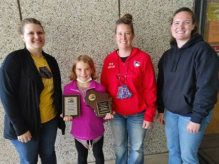Elli Rettler (second from left) was presented with the Wisconsin Ag in the Classroom Essay Contest plaque by (from left) Tri-County Elementary fourth-grade teacher, Christina Schmick; her mother, Jessica Rettler; and Wisconsin Farm Bureau Federation Promotion and Education Chair, Lynn Leahy.