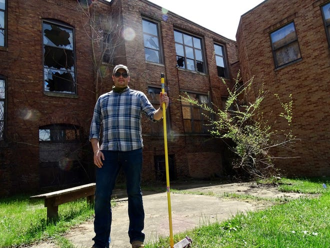 Andy Roberts stands outside of the former Munson Elementary School after the Muskingum County land bank did a walk-through to look at its condition. Although full of debris, the building is structurally sound.