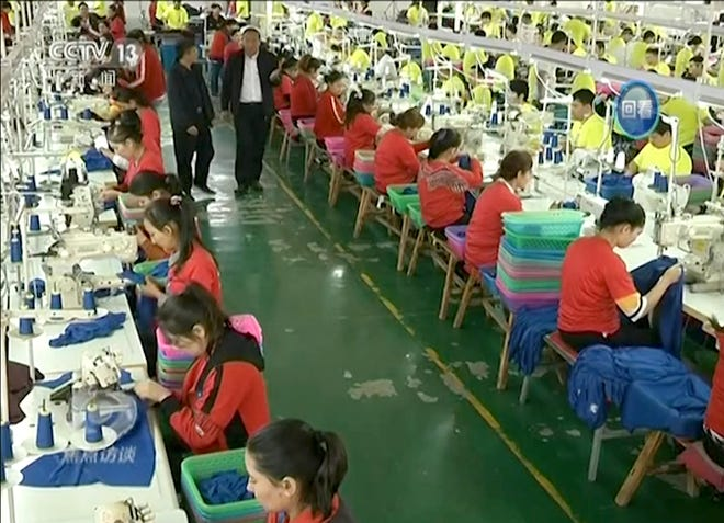 In this file image from undated video footage run by China's CCTV via AP Video, Muslim trainees work in a garment factory at the Hotan Vocational Education and Training Center in Hotan, Xinjiang, northwest China.