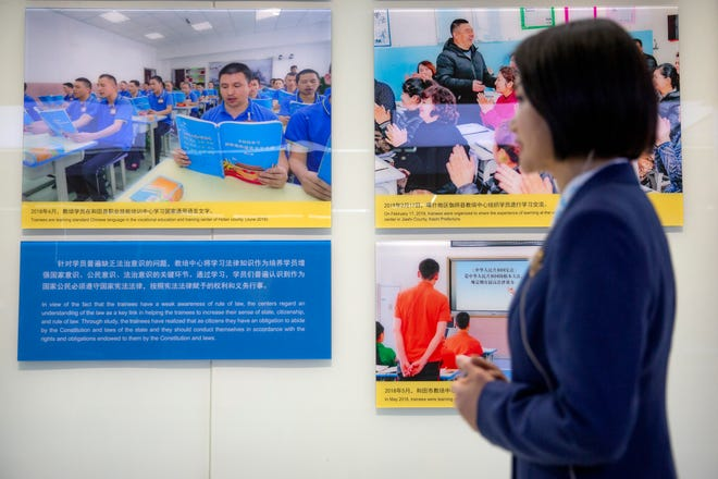 A tour guide stands near a display showing images of people at locations described as vocational training centers in southern Xinjiang at the Exhibition of the Fight Against Terrorism and Extremism in Urumqi in western China's Xinjiang Uyghur Autonomous Region on April 21, 2021.
