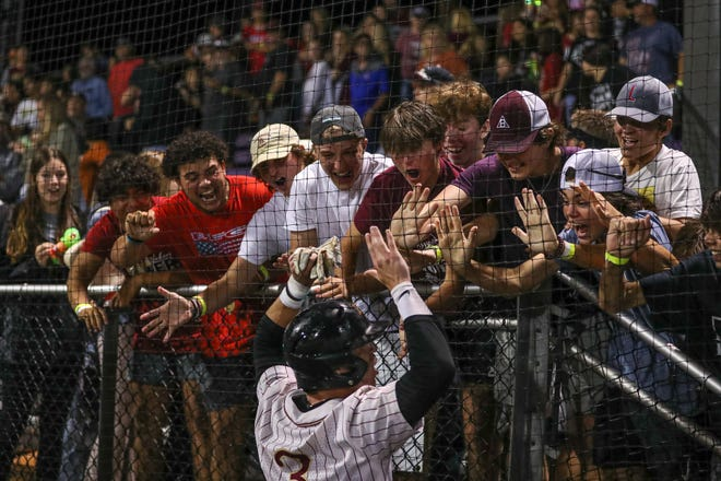 Rouse outfielder Keagan Solomon celebrates with fans after his run-scoring double in the 14th inning gave the Raiders a 2-1 victory over Dripping Springs in the Class 5A Region IV championship.