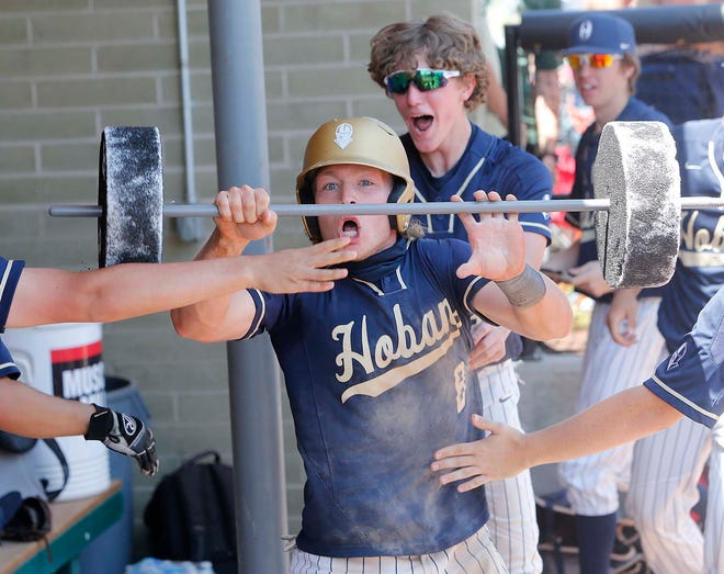 Archbishop Hoban's Caleb Kepler is given styrofoam weights to lift in the dugout to celebrate the run he scored against Salem during the eighth inning of their Division II regional final. [Karen Schiely/Beacon Journal]