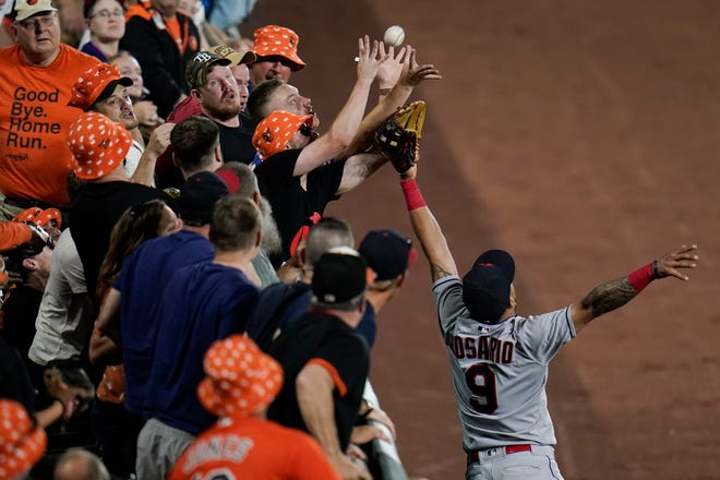 Cleveland left fielder Eddie Rosario (9) tries to catch a home run hit by the Orioles' Ryan Mountcastle as fans reach for the ball in the seventh inning Friday night. The play was reviewed for possible fan interference but was upheld and the Orioles won 3-1. [Julio Cortez/Associated Press]