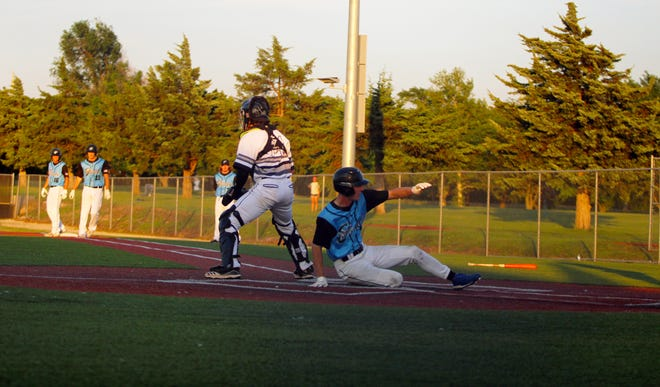 Kansas Cannons' Carson Pracht slides across home plate in the bottom of the fifth inning in Friday's 16-4 win over the Denver Cougars