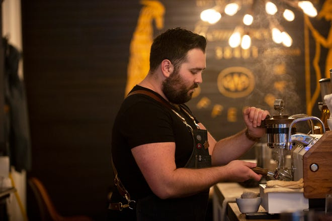 Wolf and Scout Coffee owner Lawrence Reeves prepares a latte inside the shop located at the Columbia Arts Building in Columbia, Tenn., on Friday, June 4, 2021.