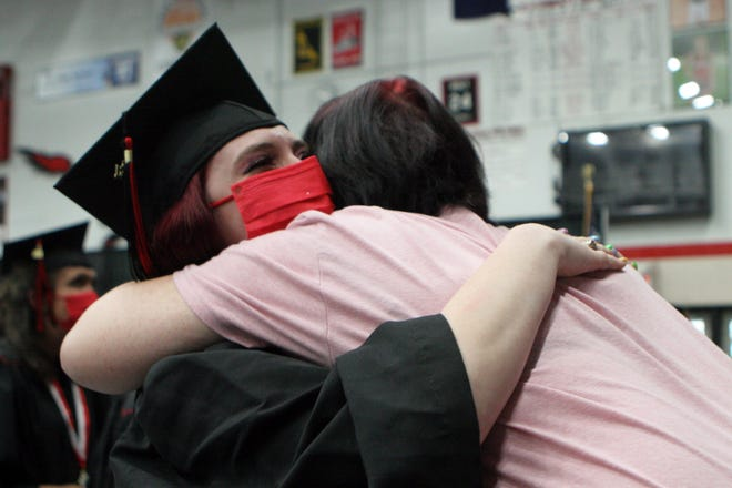 Graduate Marissa Dimmick hugs her aunt Jennifer Downs after giving her a rose during Saturday morning's commencement ceremony at Edgewood High School in Ellettsville.