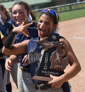 Patrina Marsh of Whiteford goofs around with teammate Chelsie Peacock with the Division 4 district final trophy after beating Sand Creek 10-0 in six innings Saturday.