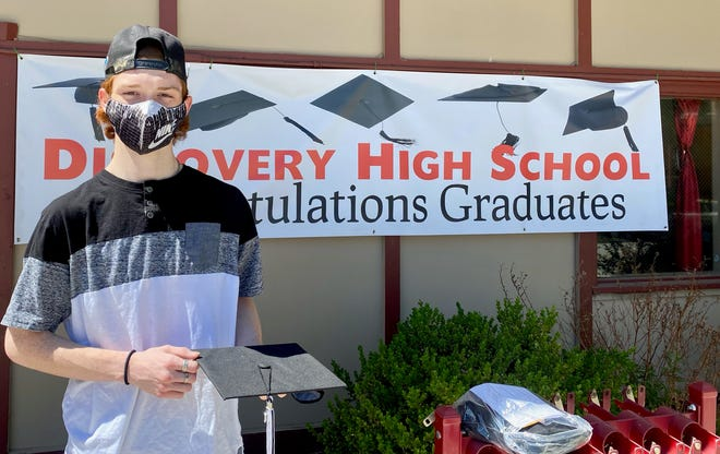 Discovery High School student  Ronnie Augusto III picks up his cap and gown.