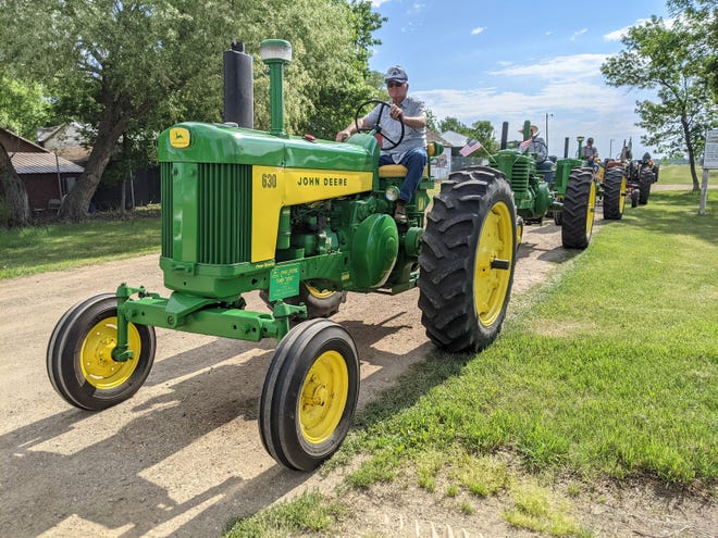 Members of the James Valley Tractor Club roll out of the Brown County Fairgrounds Saturday morning at the start of the annual Drive Out Cancer tractor drive fundraiser.
